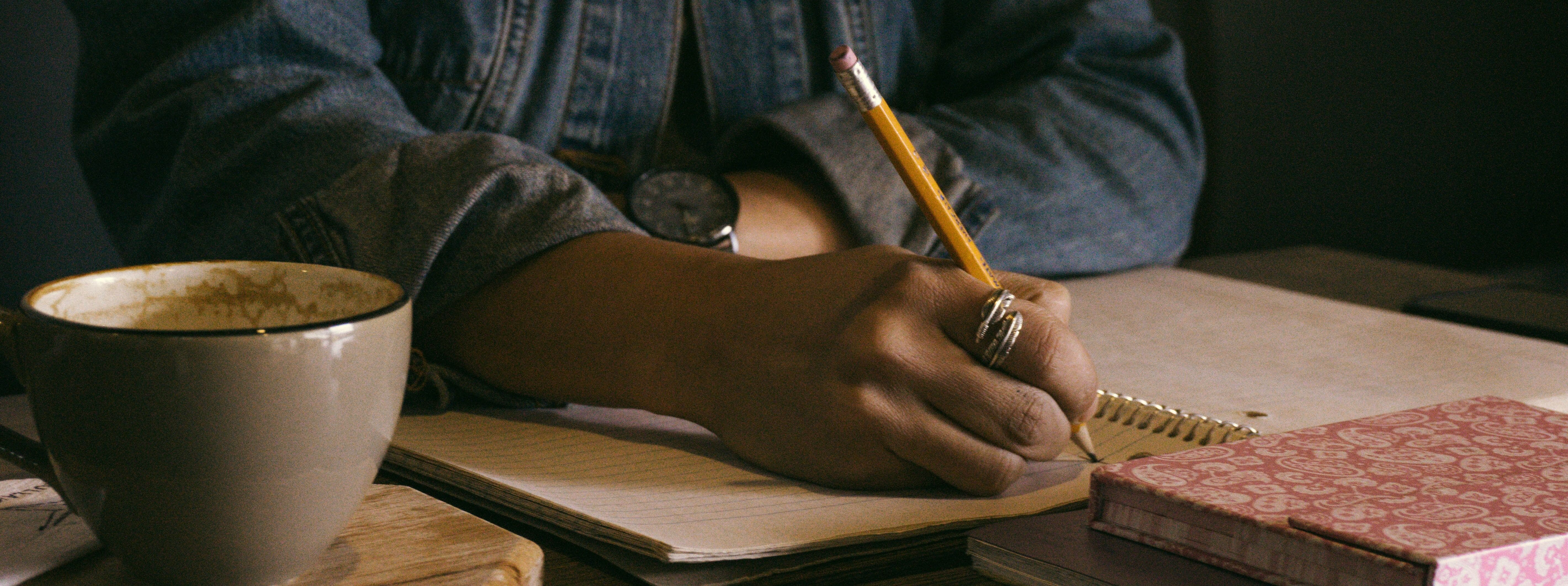 Estratégias argumentativas - imagem de uma pessoa escrevendo em um caderno com um lápis.