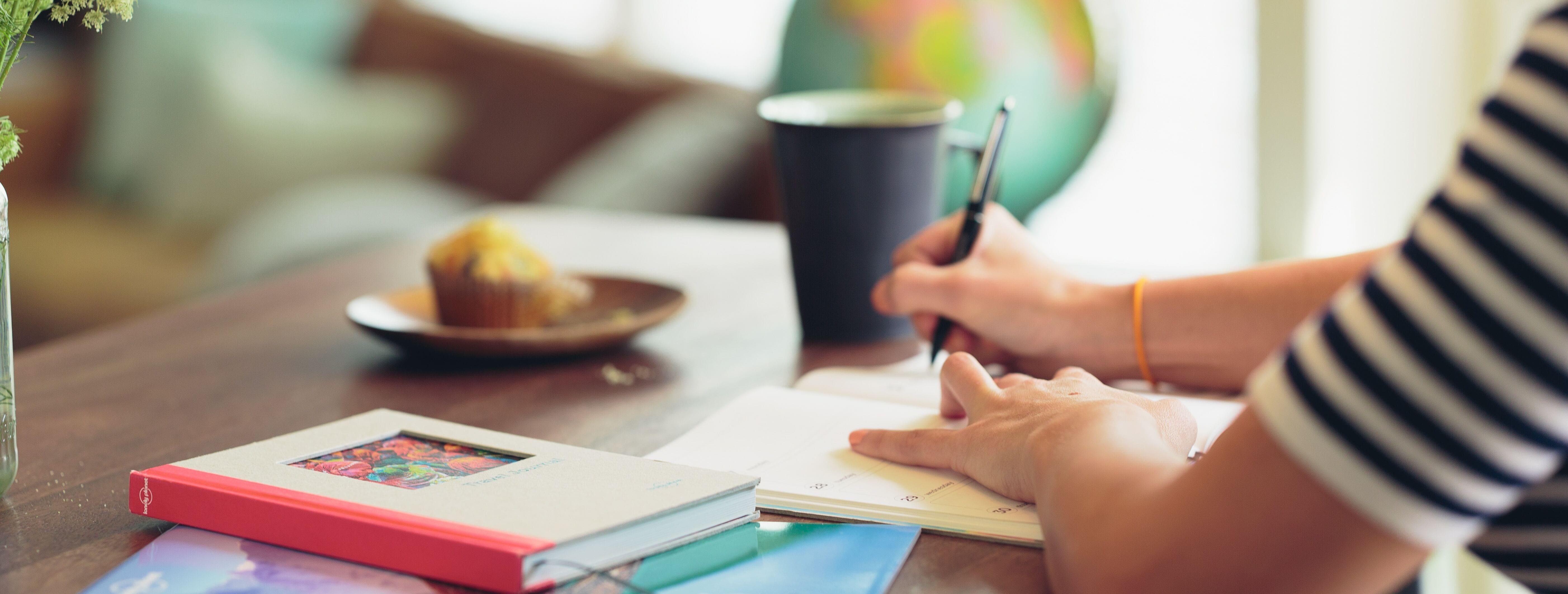 Imagem de uma mesa cheia de materiais de estudo e uma pessoa escrevendo em um caderno em cima dela.