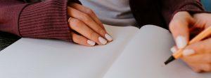 Como começar uma redação: imagem de uma pessoa escrevendo em um caderno