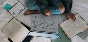 Como estudar para o Enem: Jovem estudando na cama.