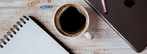 Como ter inspiração para escrever: xícara de cafá ao lado de um caderno.