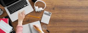 Curso de redação online: materiais de estudo sobre uma mesa.