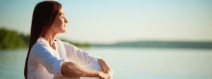 Saúde mental e a importância da cultura do autocuidado: mulher relaxando perto de uma praia.