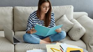 Como organizar os estudos: imagem de uma mulher estudando no sofá